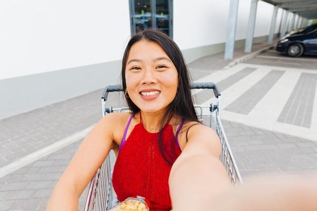Donna asiatica prendendo selfie nel carrello della spesa Foto Gratuite