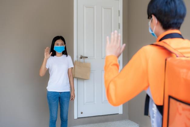 Donna asiatica ritira la busta di cibo dalla maniglia della porta e saluta i contatori senza contatto o senza contatto con la bicicletta davanti alla casa per le distanze sociali per il rischio di infezione. concetto di coronavirus Foto Premium