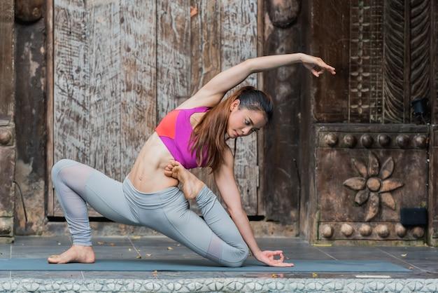 Donna asiatica sana di yoga che fa posa di yoga a casa. Foto Premium