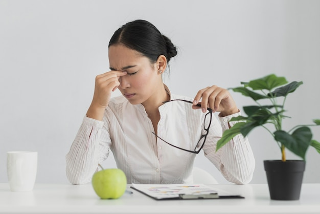 Donna asiatica stanca che si siede nell'ufficio Foto Gratuite