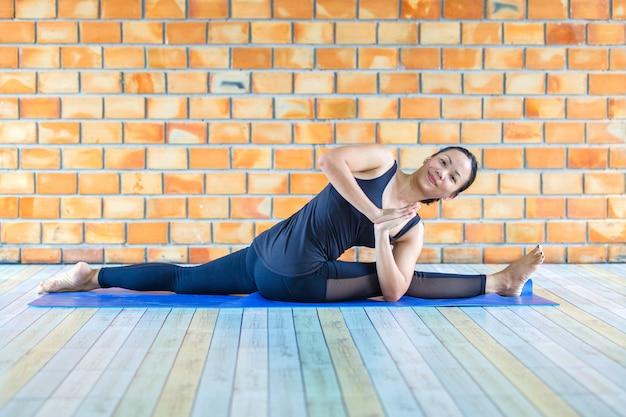 Donna asiatica tirocinante forte pratica posa yoga difficile Foto Premium