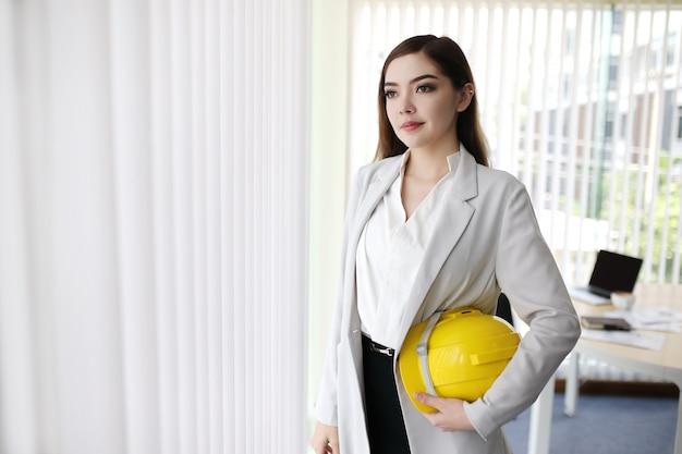 Donna astuta di affari con il casco dell'ingegnere della tenuta della mano del vestito che sta nell'ufficio di affari Foto Premium