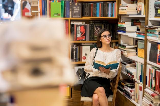 Donna astuta in vetri che si siedono con il libro in biblioteca Foto Gratuite