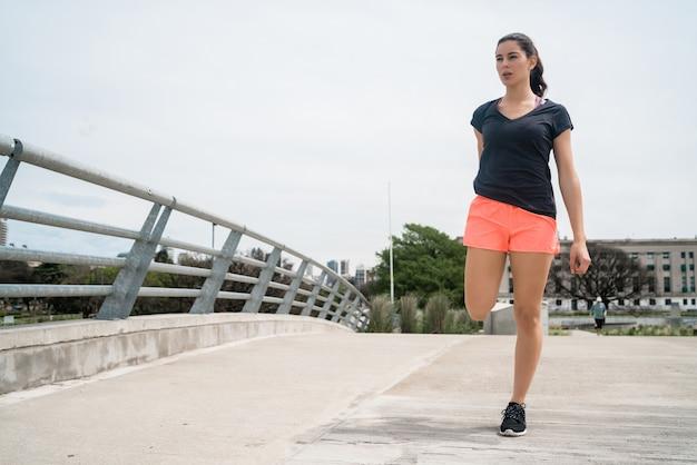 Donna atletica che allunga le gambe prima dell'esercizio Foto Gratuite