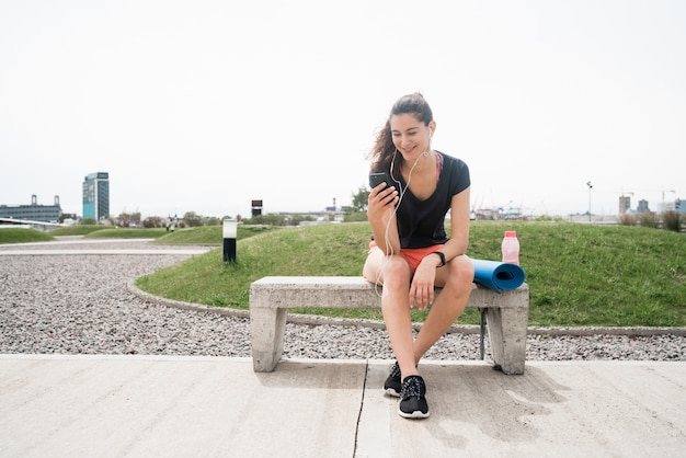 Donna atletica che per mezzo del suo telefono Foto Gratuite
