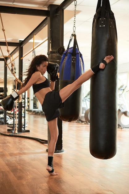 Donna atletica che si prepara duramente a calciare il sacco da boxe Foto Gratuite