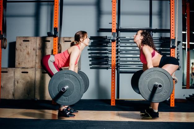 Donna atletica che solleva i bilancieri pesanti sulle spalle in palestra spaziosa leggera Foto Premium