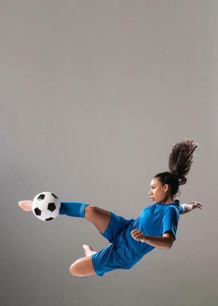 Donna atletica della foto a figura intera che dà dei calci alla palla Foto Gratuite