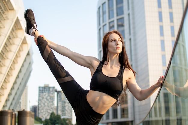 Donna atletica impegnata in atletica leggera, si allena al mattino per strada, una donna fa stretching e trucchi di ginnastica Foto Premium