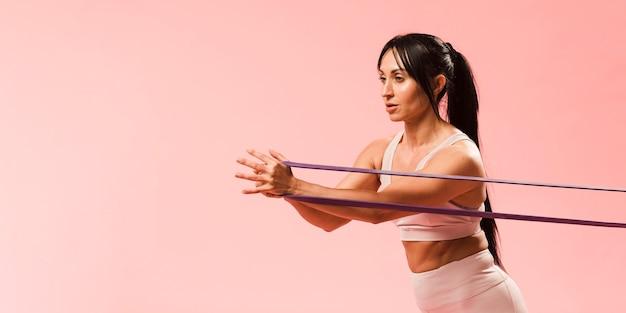 Donna atletica in attrezzatura della palestra che tira la banda di resistenza Foto Gratuite