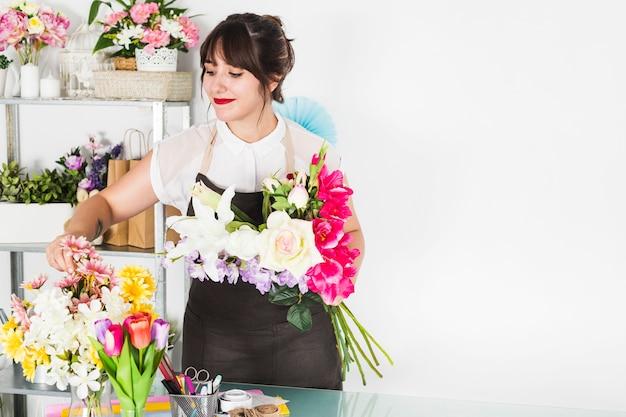 Donna attraente che organizza i fiori nel negozio floreale Foto Gratuite