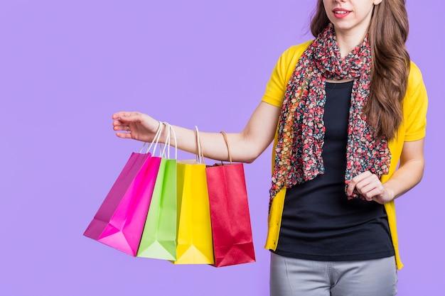 Donna attraente che porta il sacco di carta variopinto contro fondo porpora Foto Gratuite