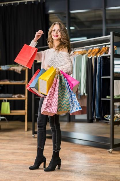 Donna attraente che trasporta la dimensione differente del sacco di carta nel negozio di boutique Foto Gratuite