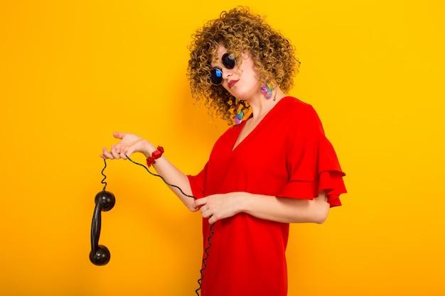 Donna attraente con brevi capelli ricci con il telefono Foto Premium