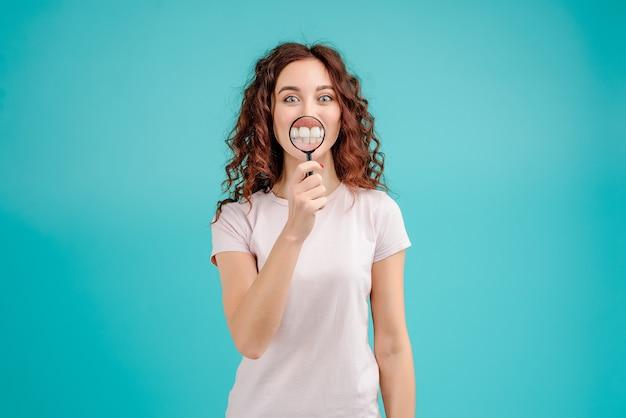 Donna attraente con capelli ricci che mostra i denti attraverso la lente di ingrandimento Foto Premium