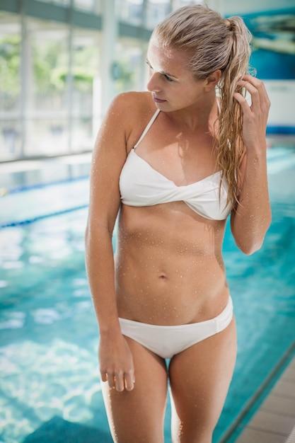 Donna attraente in piedi e guardando lontano in piscina Foto Premium