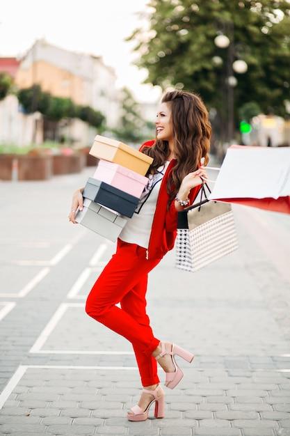 Donna attraente sorridente in scatole di scarpe eleganti della tenuta del vestito di sport rosso e sacchetti della spesa nella via. Foto Premium