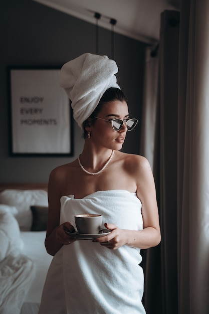 Donna avvolta in un asciugamano che beve caffè Foto Gratuite