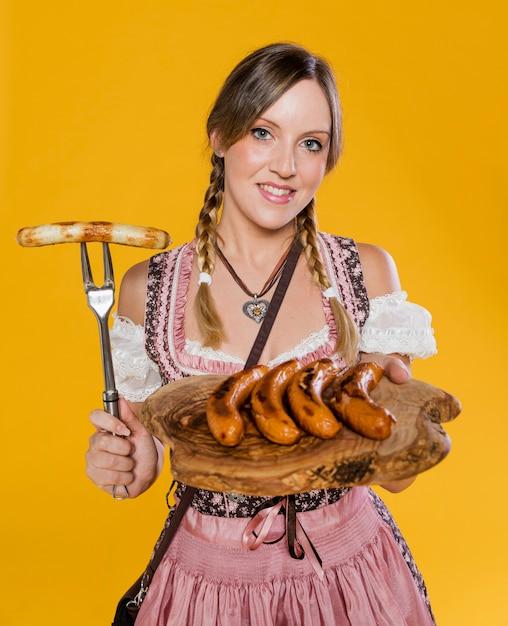 Donna bavarese che tiene alimento tradizionale Foto Gratuite