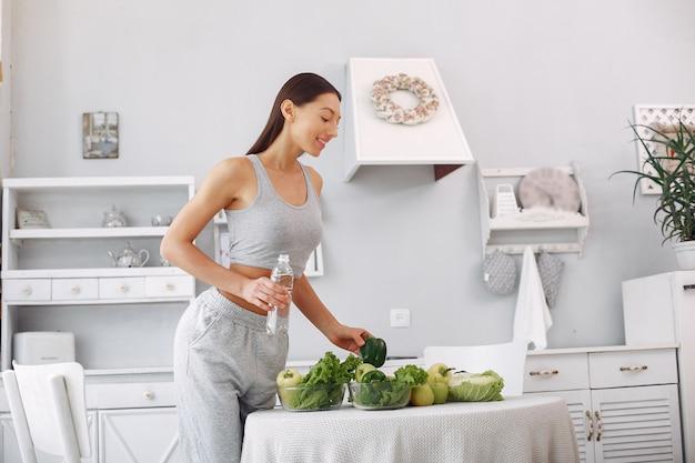 Donna bella e sportiva in una cucina con verdure Foto Gratuite