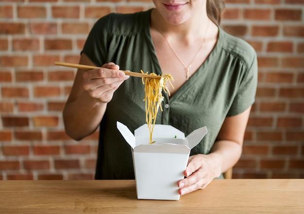 Donna bianca che mangia chow mein Foto Gratuite