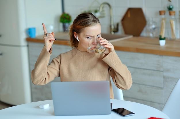 Donna bionda adorabile che lavora con il suo computer portatile mentre sedendosi nella cucina nel suo appartamento Foto Premium