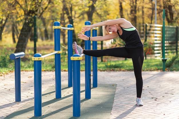 Donna bionda atletica che fa allungando le esercitazioni Foto Gratuite