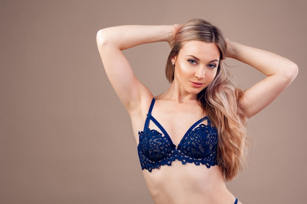 Donna bionda attraente che posa in biancheria alla moda in studio Foto Premium