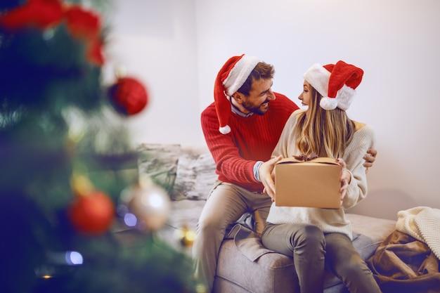Donna bionda caucasica sveglia stupita che si siede sul sofà in salone e che riceve regalo dal suo ragazzo. entrambi hanno cappelli di babbo natale in testa. in primo piano è l'albero di natale. interno soggiorno. Foto Premium