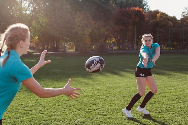 Donna bionda che passa un pallone da calcio Foto Gratuite