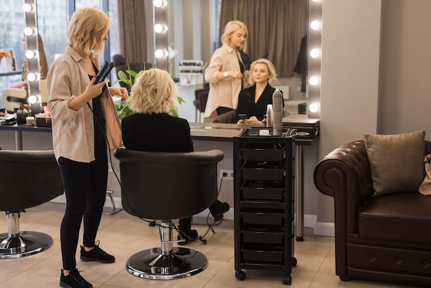 Donna bionda che si fa fare i capelli Foto Gratuite