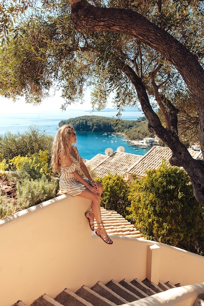 Donna bionda che si siede sulle scale con la vista di mare stupefacente dietro Foto Premium
