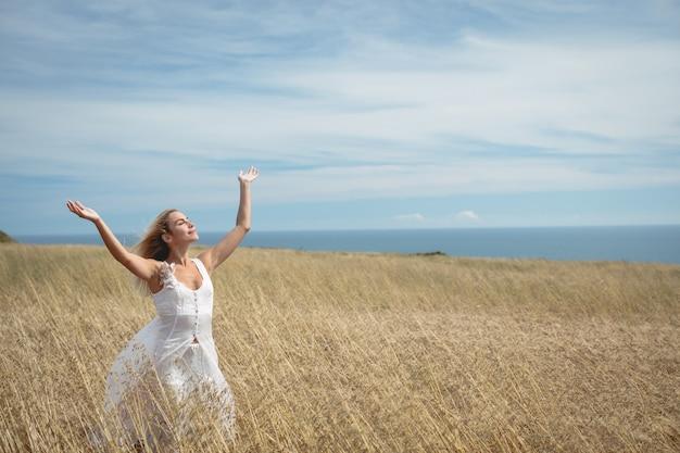 Donna bionda che sta nel campo con le armi alzate Foto Gratuite