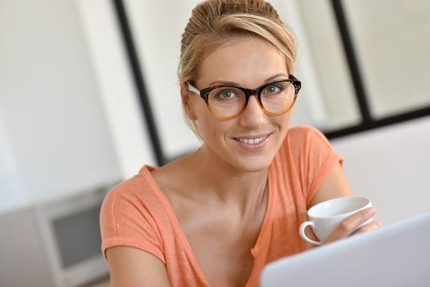 Donna bionda con gli occhiali che lavora da casa con il computer portatile Foto Premium
