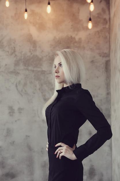 Donna bionda con la posa nera del vestito Foto Gratuite