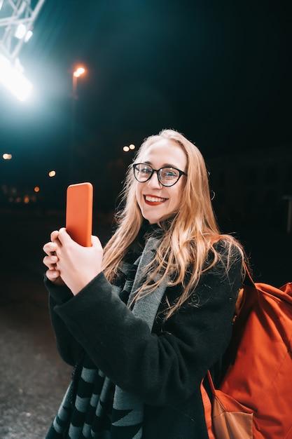 Donna bionda con lo smartphone di notte in strada. Foto Gratuite