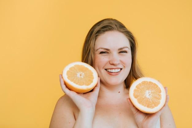 Donna bionda curvy che tiene due arance fresche Foto Gratuite