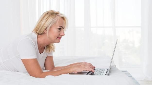 Donna bionda del colpo medio a letto con il computer portatile Foto Gratuite