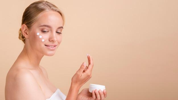 Donna bionda del primo piano con crema sul suo fronte Foto Gratuite