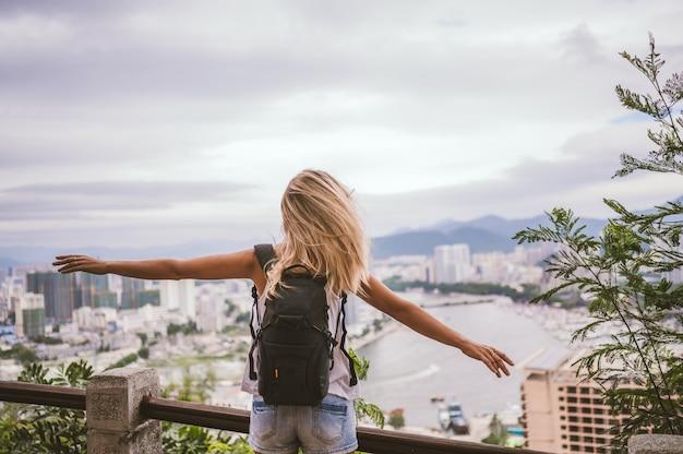 Donna bionda del viaggiatore con zaino e sacco a pelo che cammina trascurando la città. avventura di viaggio in cina, bella destinazione turistica asia, viaggio di vacanze estive. libertà e concetto di persone felici Foto Premium