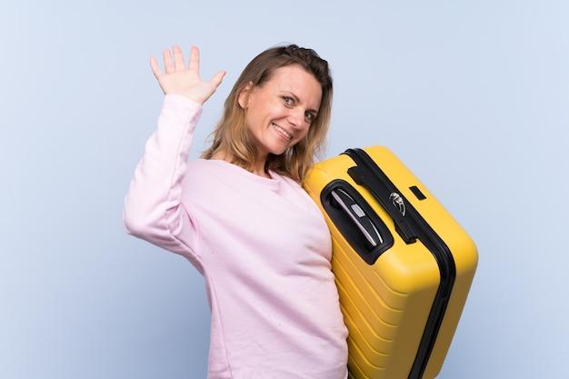 Donna bionda del viaggiatore sopra la parete isolata Foto Premium