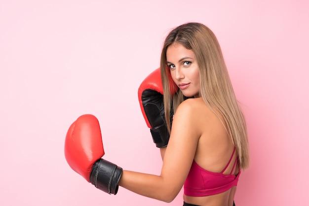 Donna bionda di giovane sport con i guantoni da pugile sopra il rosa isolato Foto Premium