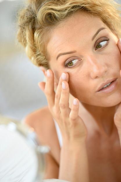Donna bionda di mezza età che mette le estetiche sopra Foto Premium