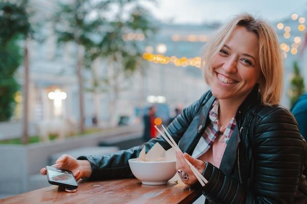 Donna bionda europea che mangia riso pho bo con il caffè vietnamita della via della tavola di legno dei bastoni a mosca. Foto Premium