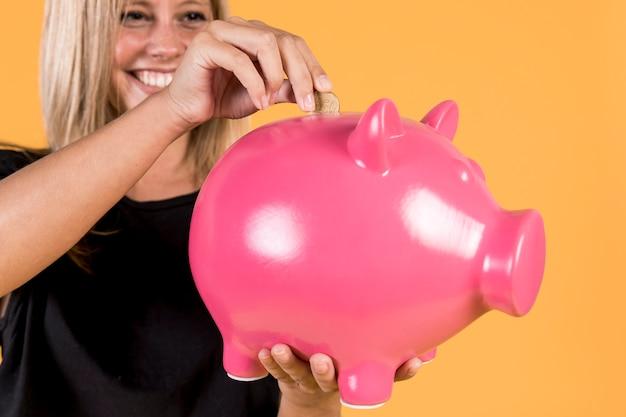 Donna bionda felice che inserisce moneta dentro il porcellino salvadanaio rosa Foto Gratuite