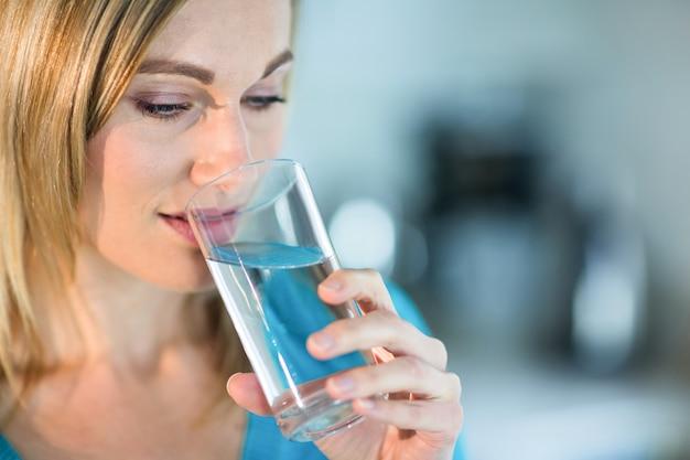 Donna bionda graziosa che beve un bicchiere d'acqua Foto Premium