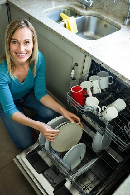 Donna bionda graziosa che svuota la lavastoviglie Foto Premium
