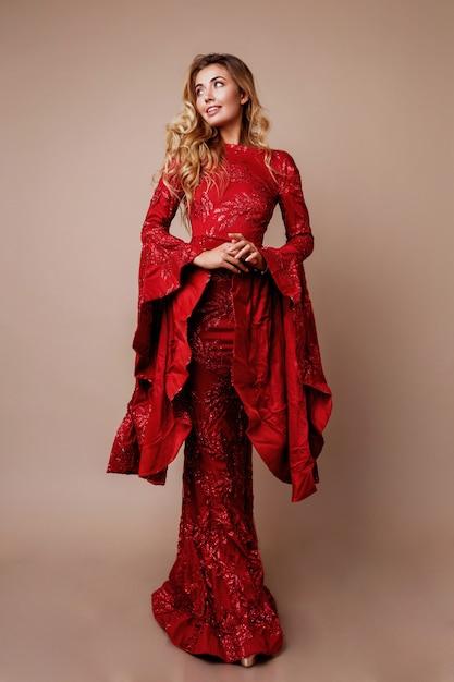 Donna bionda graziosa nella posa elegante del vestito dal nuovo anno. maniche larghe insolite. capelli mossi. a tutta altezza. Foto Gratuite
