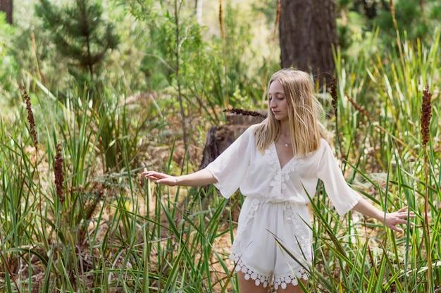 donna bionda guardando verso il basso nel parco Foto Gratuite