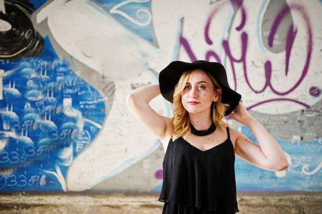 Donna bionda in abito nero, collane e cappello contro il muro di graffiti. Foto Premium